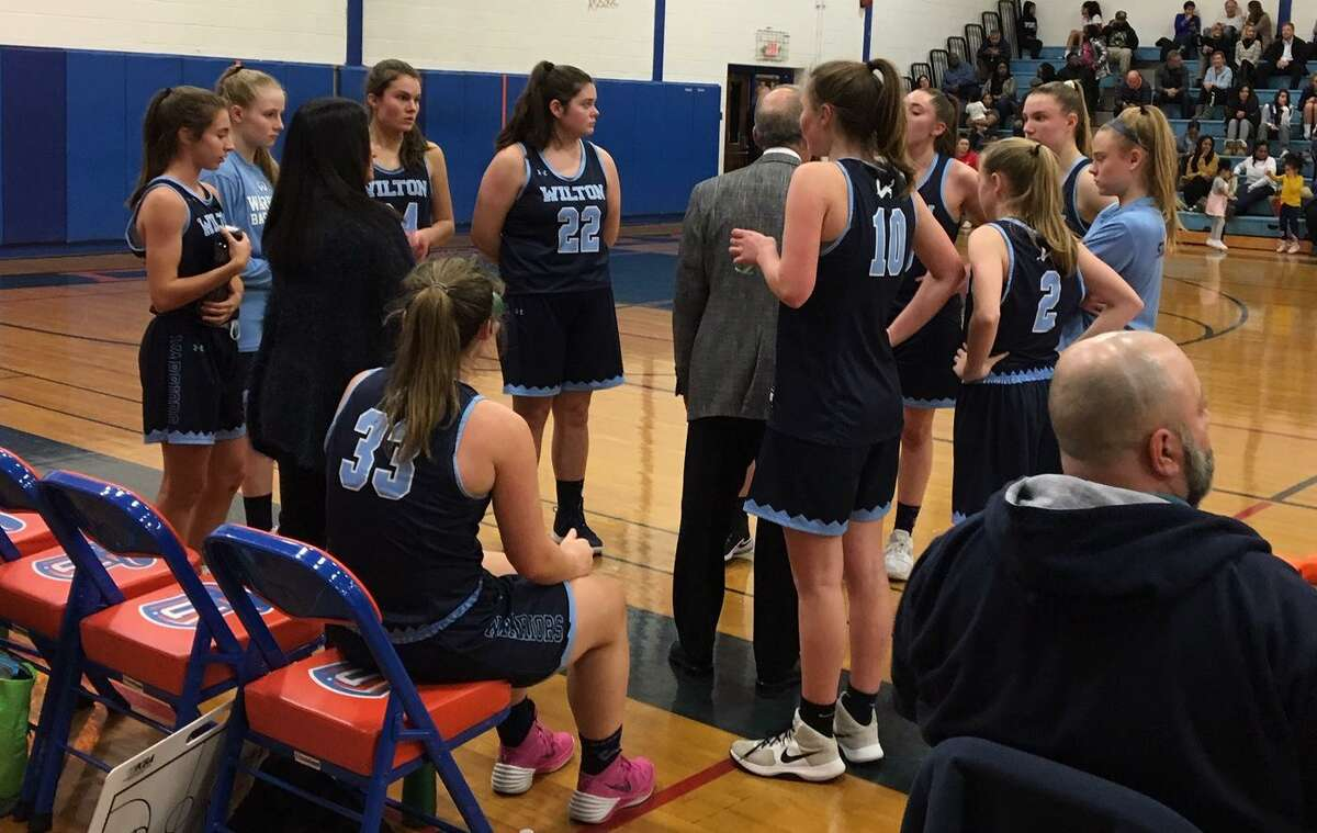 The Wilton girls basketball team gathers around coach Fred Francello during a timeout in Thursday's game at Danbury.