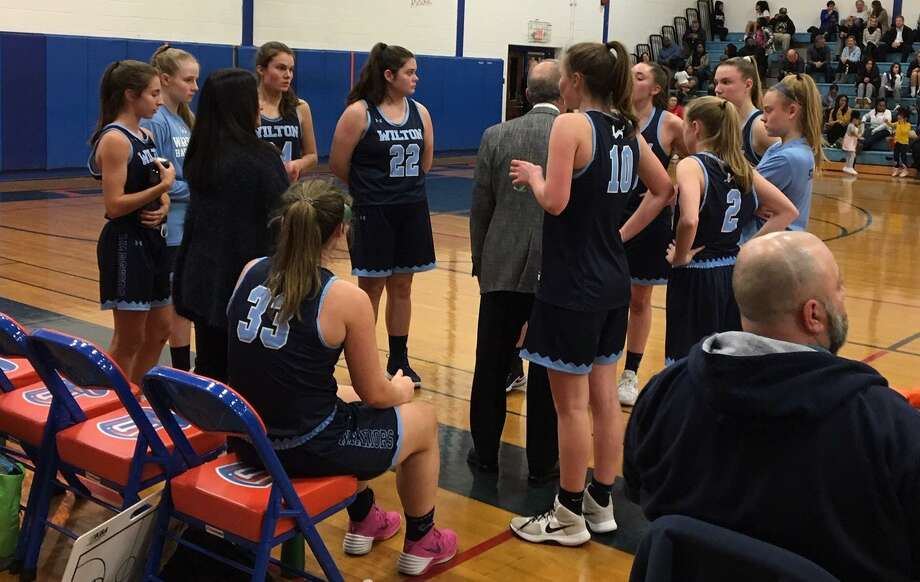 The Wilton girls basketball team gathers around coach Fred Francello during a timeout in Thursday's game at Danbury. Photo: Tim Murphy / Hearst Connecticut Media