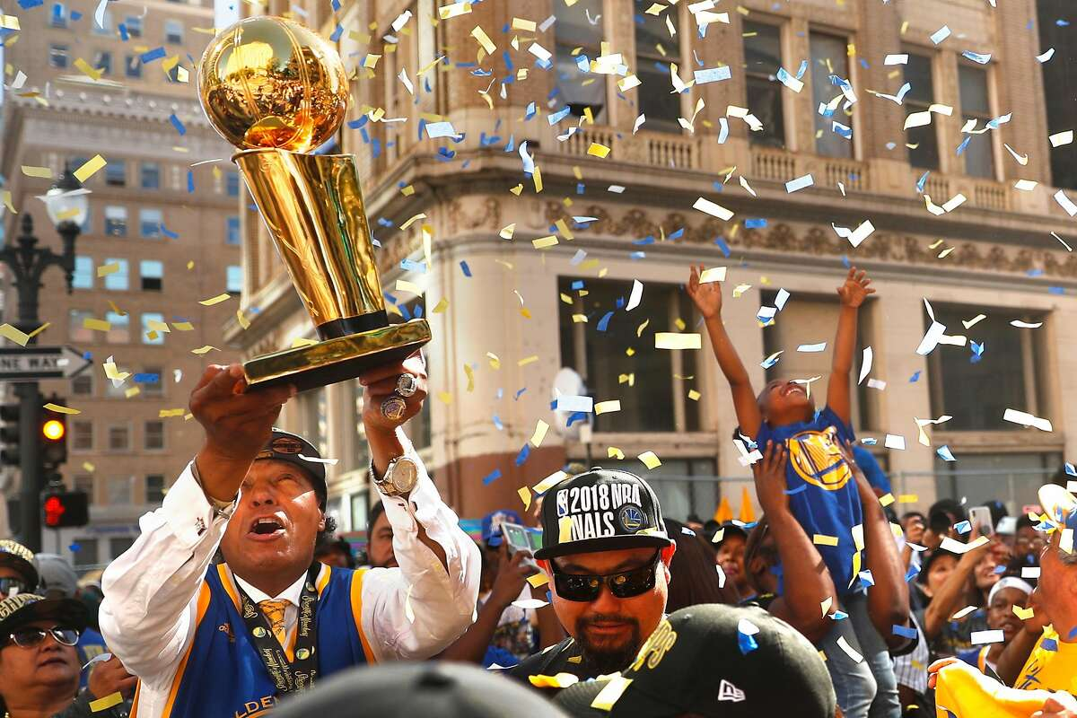 Charles Chapman of Oakland holds up a replica Larry O'Brien trophy as fans create their own confetti celebration before Golden State Warriors' NBA Championship parade in Oakland, CA on Tuesday, June12, 2018.