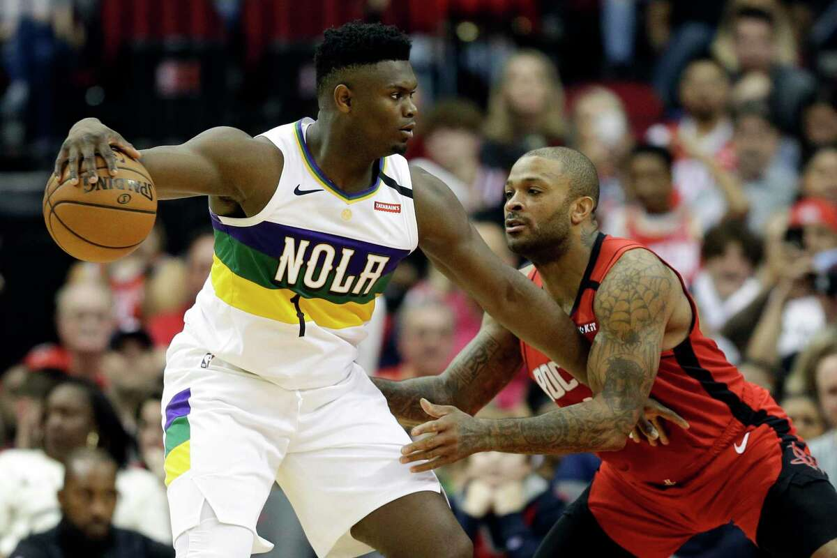 New Orleans Pelicans forward Zion Williamson (1) dribbles as Houston Rockets forward P.J. Tucker defends during the second half of an NBA basketball game, Sunday, Feb. 2, 2020, in Houston.