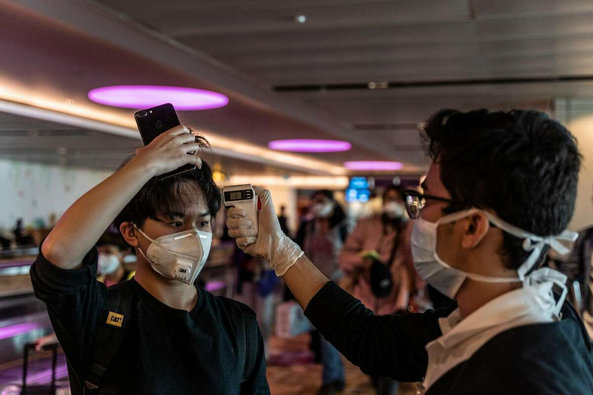 An arriving passenger has his temperature checked at Changi Airport, Singapore, Jan. 29, 2020. The World Health Organization has declared the coronavirus epidemic a global health emergency, but the message does not seem to be resonating in some parts of Southeast Asia, a magnet for Chinese tourists and workers. (Adam Dean/The New York Times)