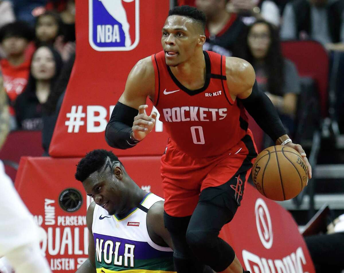 After beating heralded Pelicans rookie Zion Williamson, left, to a rebound, Rockets guard Russell Westbrook heads upcourt Sunday at Toyota Center