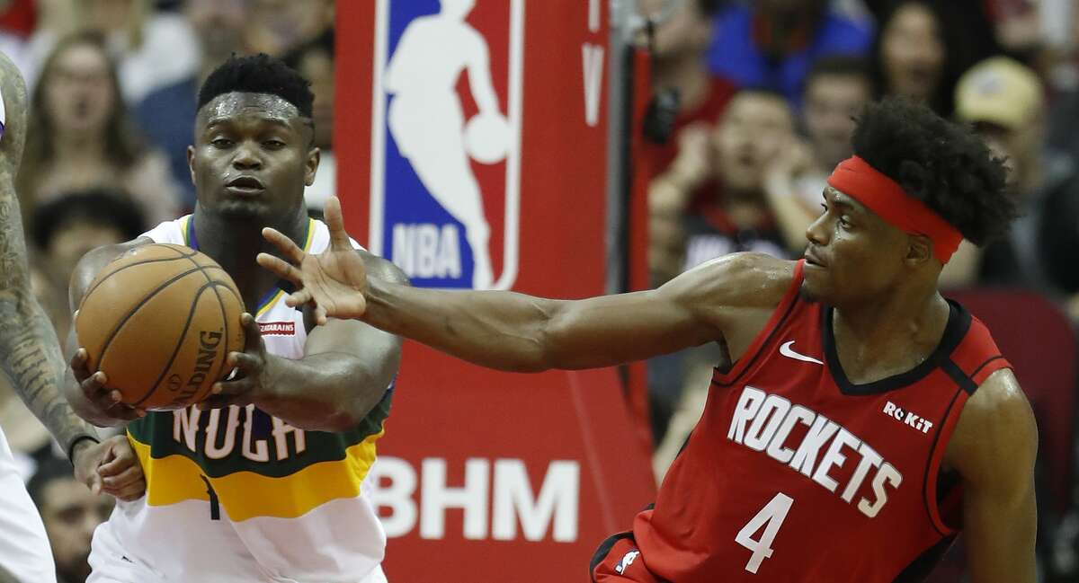 New Orleans Pelicans forward Zion Williamson (1) and Houston Rockets forward Danuel House Jr. (4) battle for a rebound during the second half of an NBA basketball game at Toyota Center in Houston, Sunday, Feb. 2, 2020.