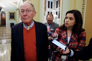 Sen. Lamar Alexander, R-Tenn., talks to reporters as he walks past the Senate chamber prior to the start of the impeachment trial of President Donald Trump at the U.S. Capitol on Friday.