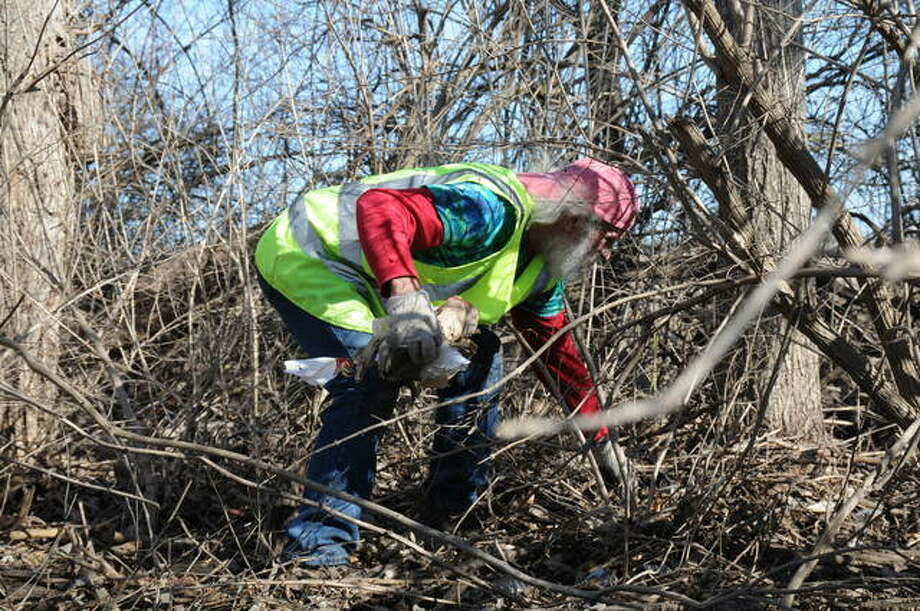 Trinity's Way volunteer John Scanlon, of Godfrey, picks trash from roadside brush along Godfrey Road, across from the Godfrey Walmart, Sunday. Trinity's Way is a nonprofit organization named for Trinity Marie Buel, 17, who died Feb. 17, 2018, in a traffic crash on Homer M. Adams Parkway, in Alton. Photo: David Blanchette|For The Telegraph