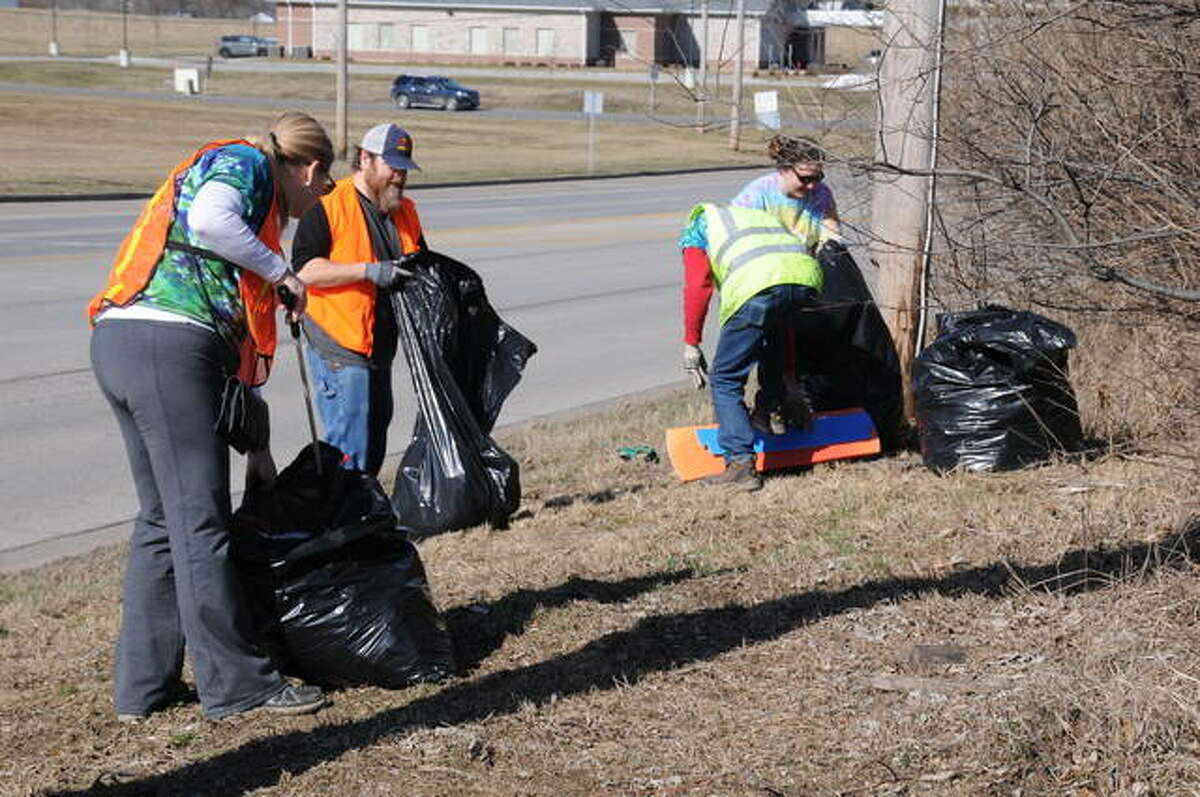 Trinity's Way volunteers fill bags with trash during the nonprofit organization's cleanup Sunday along Godfrey Road. Trinity's Way has another cleanup scheduled at 10 a.m. Saturday, Feb. 15, at Alton's Piasa Park.