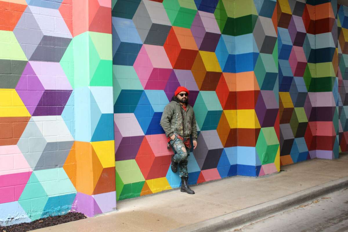Dallas artist Ricardo Paniagua in front of his mural 'Super Deluxe' in the West Village shopping area.