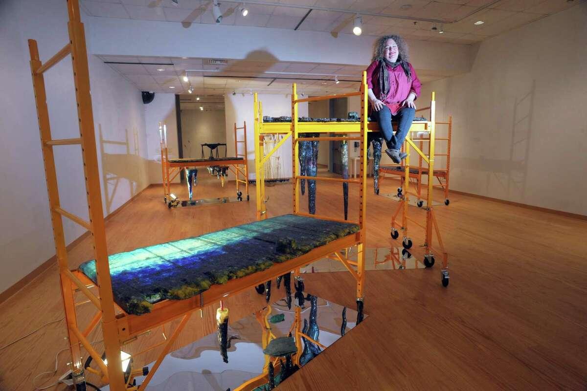 Rachel Owens poses on top of one off her sculpture installations, part of her Hypogean Tip exhibit on display in Housatonic Museum of Art.