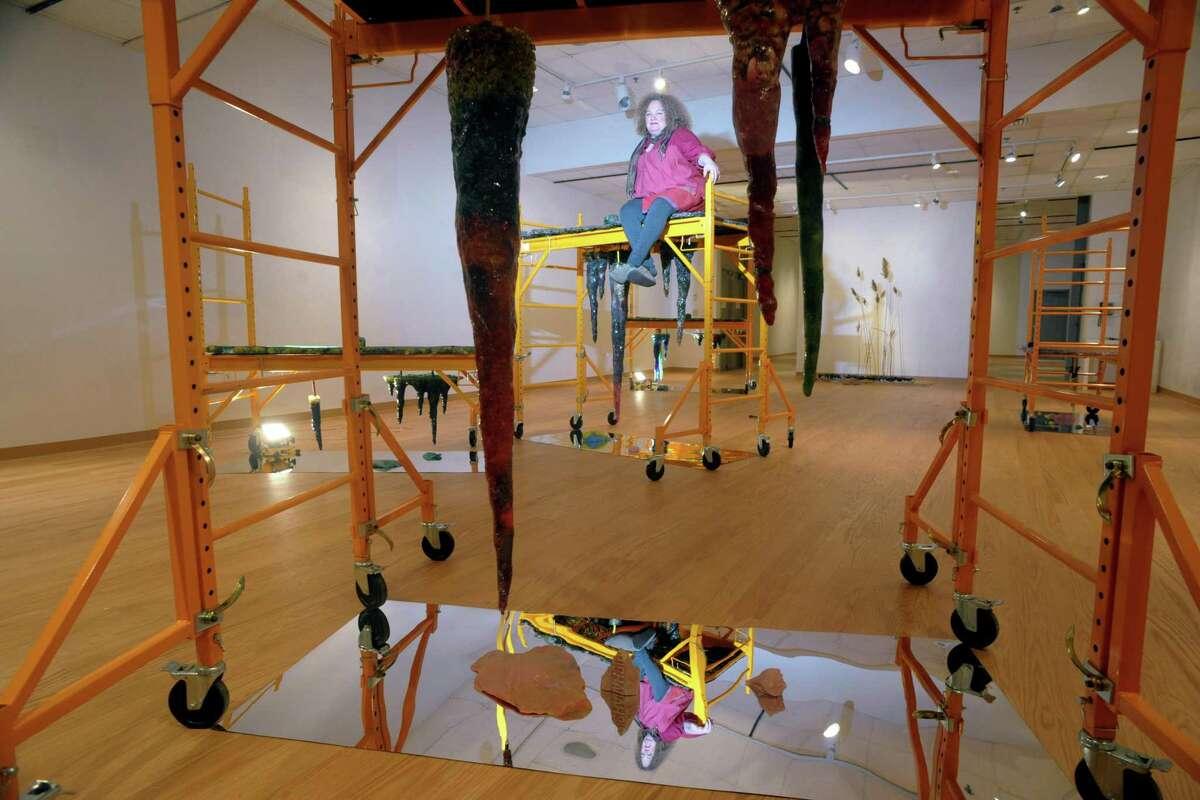 Rachel Owens poses on top of one off her sculpture installations, part of her Hypogean Tip exhibit on display in Housatonic Museum of Art's Burt Chernow Gallery, in Bridgeport, Conn. Jan. 23, 2020.