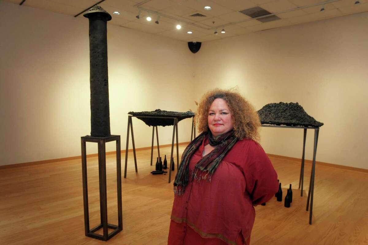 Rachel Owens poses in front of several of her sculpture installations, part of her Hypogean Tip exhibit on display in Housatonic Museum of Art's Burt Chernow Gallery, in Bridgeport, Conn. Jan. 23, 2020.