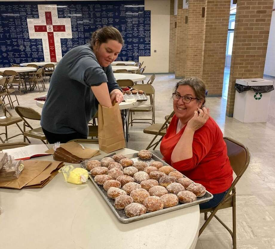 The Paczki are back at Manistee Catholic Central after a group of parents revived the annual fundraiser using the original recipe to help raise funds for the middle school football team. Elysia LaPan and Carol Slivka are shown packaging orders up in the initial sales. Because of the popularity of the initial sales the group is making more Paczki for another sale. Photo: Ken Grabowski/News Advocate
