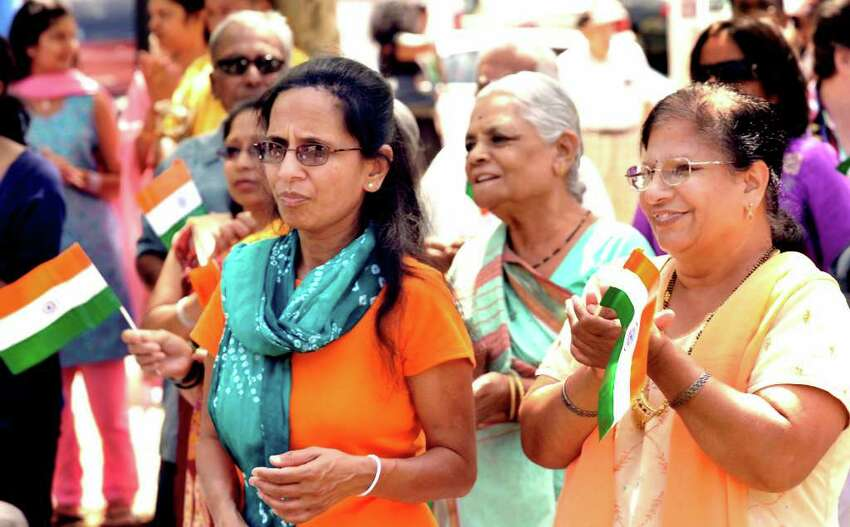 Mina Bhavgav, left, and Upma Bhavgav, right, of Danbury, applaud the Indian National anthem during the Jai Ho Festival sponsored by the Indian Association of Western Connecticut, on the Danbury Green, Saturday, Aug. 14, 2010.