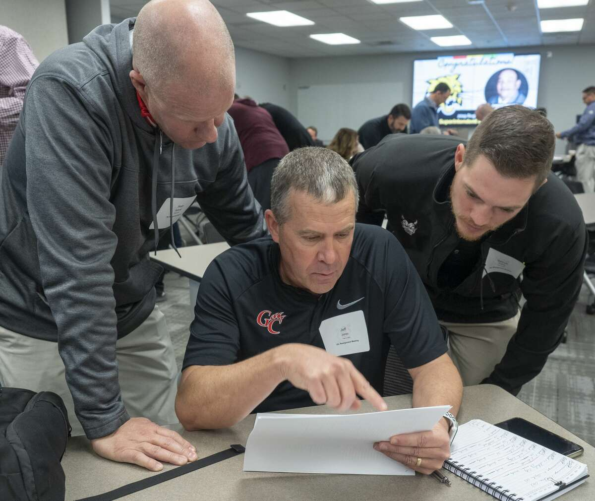Garden City coach Jeff Jones, center, Glasscock County superintendent Scott Bicknell, left and Rankin coach Garrett Avalos look over the paperwork 02/03/2020 morning, distributed by the UIL governing body, on what schools will be classified or reassigned in the district for the 2020-2022 school years. Tim Fischer/Reporter-Telegram