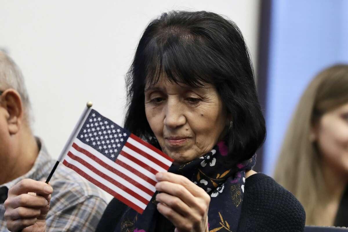 Feruza Talipova, from Uzbekistan, looks closely at an American flag before a naturalization ceremony, Friday, Jan. 17, 2020, in Cleveland. (AP Photo/Tony Dejak)