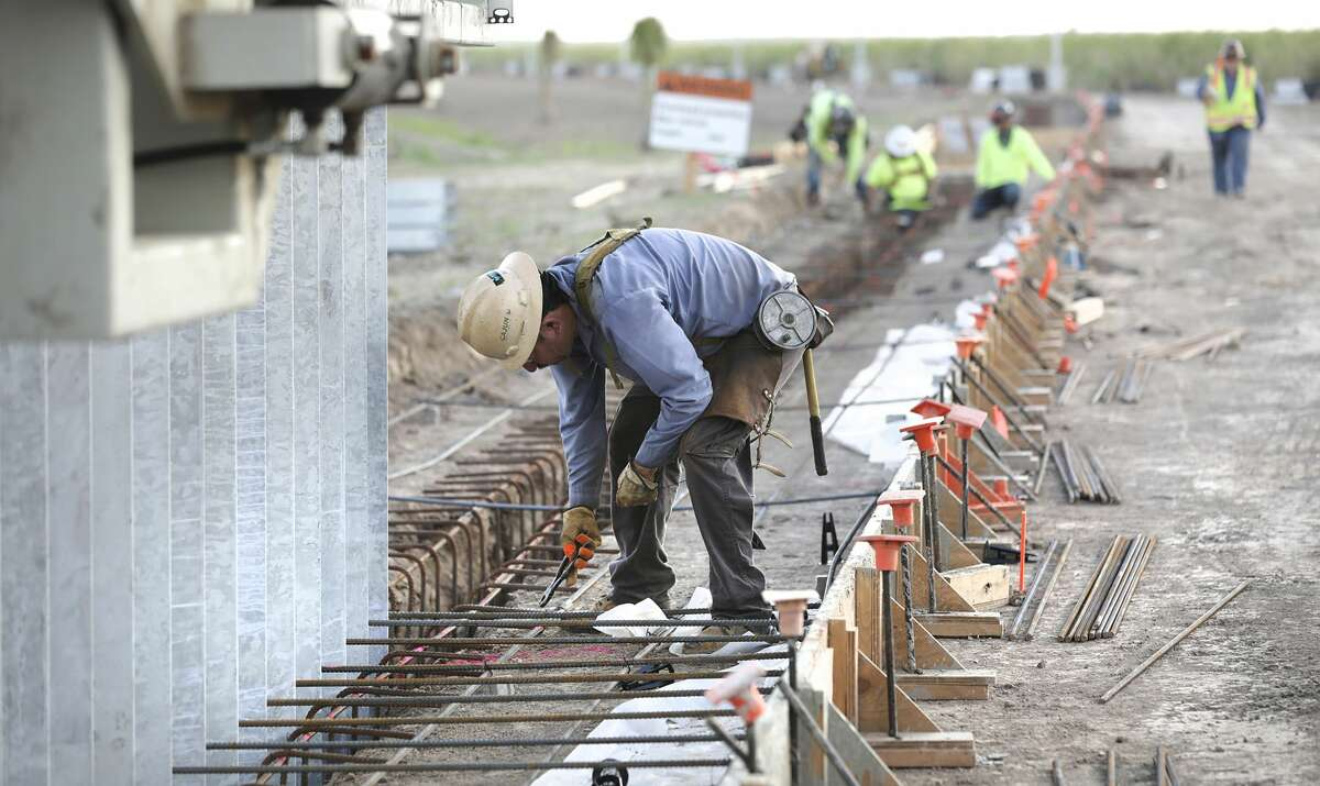 Workers from Fisher Sand and Gravel Co. are constructing 3.5 miles of border wall along the River Grande south of Mission, Texas.