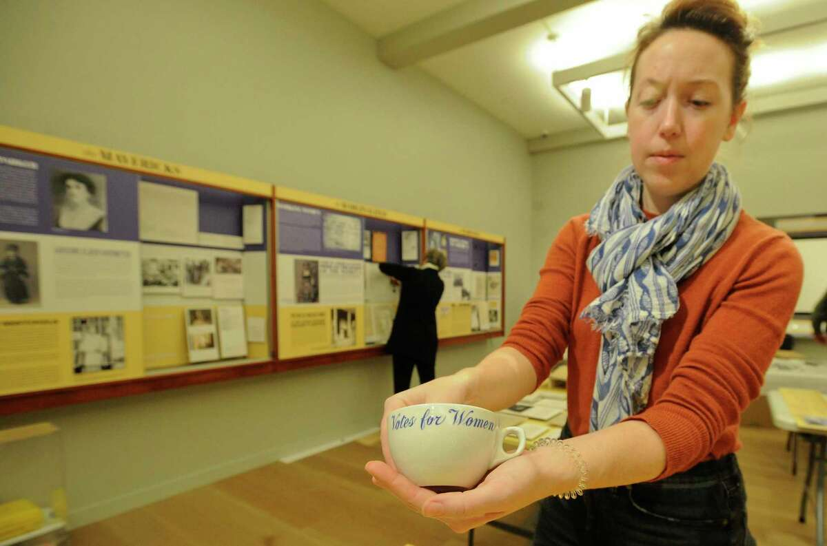 """Maggie Dimock, Curator of Exhibition and Collections for the Greenwich Historical Society, over sees the final installation of the """"An Unfinished Revolution: The Women's Suffrage Centennial"""" exhibition at the museum in Greenwich, Connecticut on Jan. 30, 2020."""