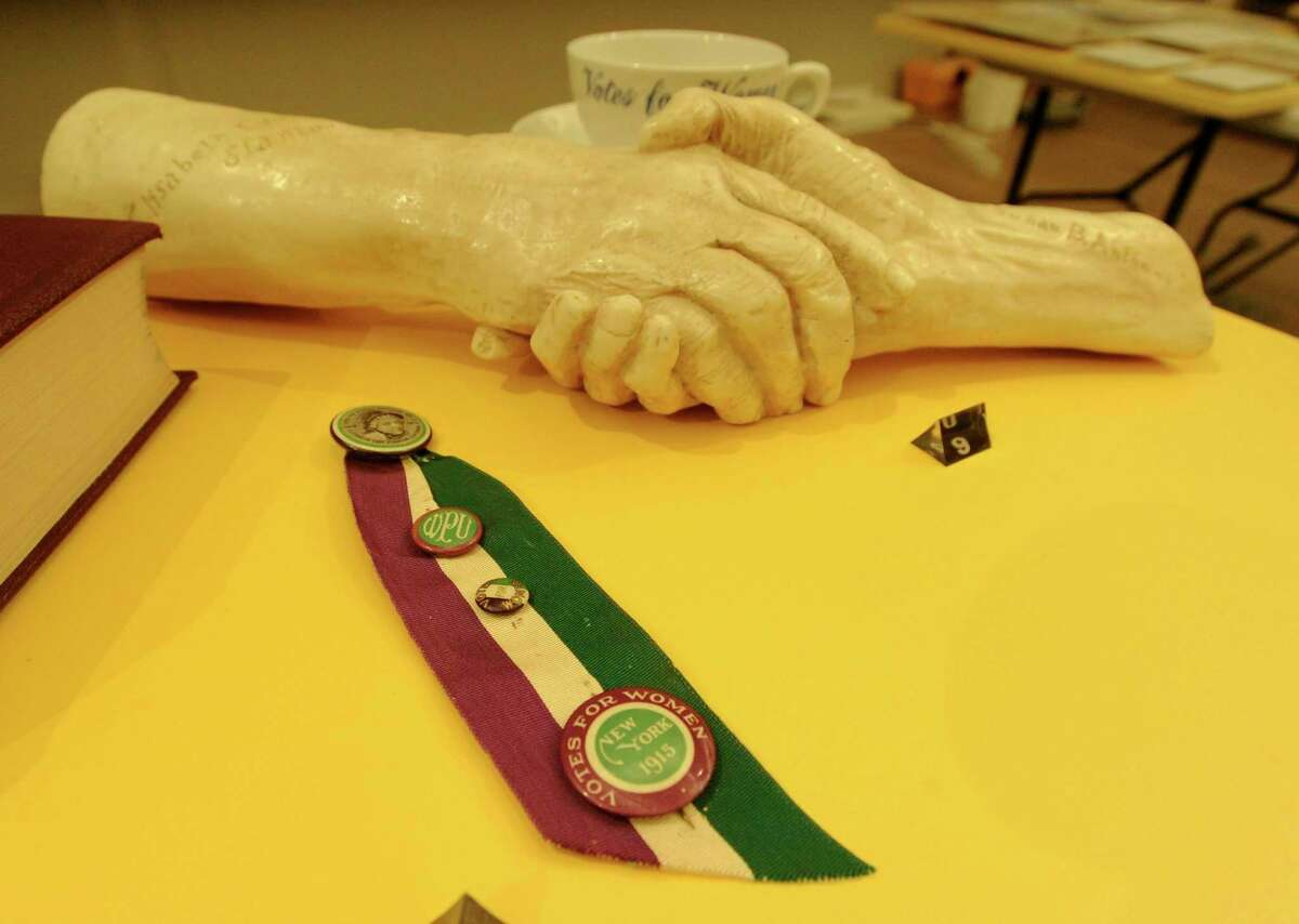 A copy reproduction of the Handshake between Elizabeth Cady Stanton and Susan B. Anthony is displayed alongside of other artifacts that are part of the