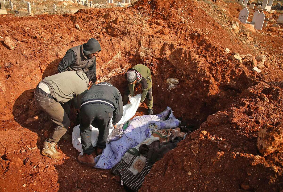 EDITORS NOTE: Graphic content / Syrians bury the bodies of nine civilians killed in an air strike in Syria's rebel-heldnorthern Aleppo province in a collective grave in the village of Urum al-Kubra on February 3, 2020, following one of the deadliest rounds of bombardment since an ongoing government offensive against the area started last month. (Photo by AAREF WATAD / AFP) (Photo by AAREF WATAD/AFP via Getty Images)