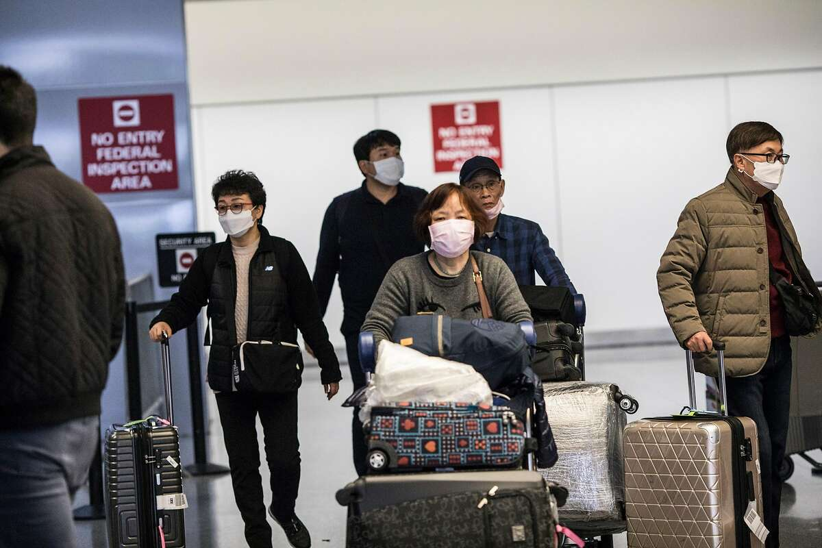 Passengers exit customs at San Francisco Airport's international terminal last week. Wait times to clear immigration and customs are hard to predict in the wake of new coronavirus-related travel restrictions.