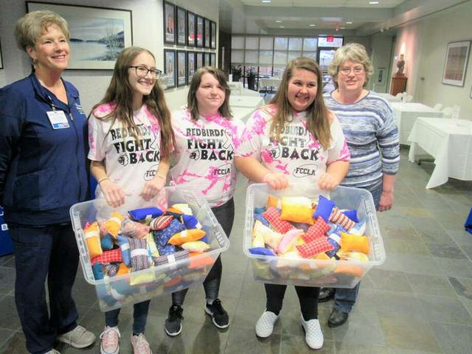 From left, Donna Campbell of Alton Memorial Hospital is shown with Alton High School Family, Career, and Community Leaders of America members Paige Ontis, Maddie Besaw and Abby Janagin and their advisor, Regina Birch, along with 165 port pillows the students donated to the hospital's cancer center.