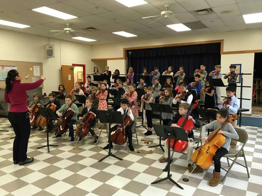String teacher Ms. Dawn Hanley, leading the Holmes 3rdgrade string students in their debut performance on January 31 Photo: Holmes