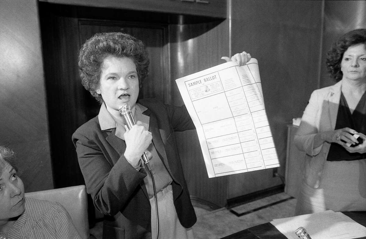 City Secretary Anna Russell, shown here on Oct. 5, 1981, holds up a sample ballot to explain the process where the press will draw names to determine the candidates' assignments on the ballot for the upcoming election.
