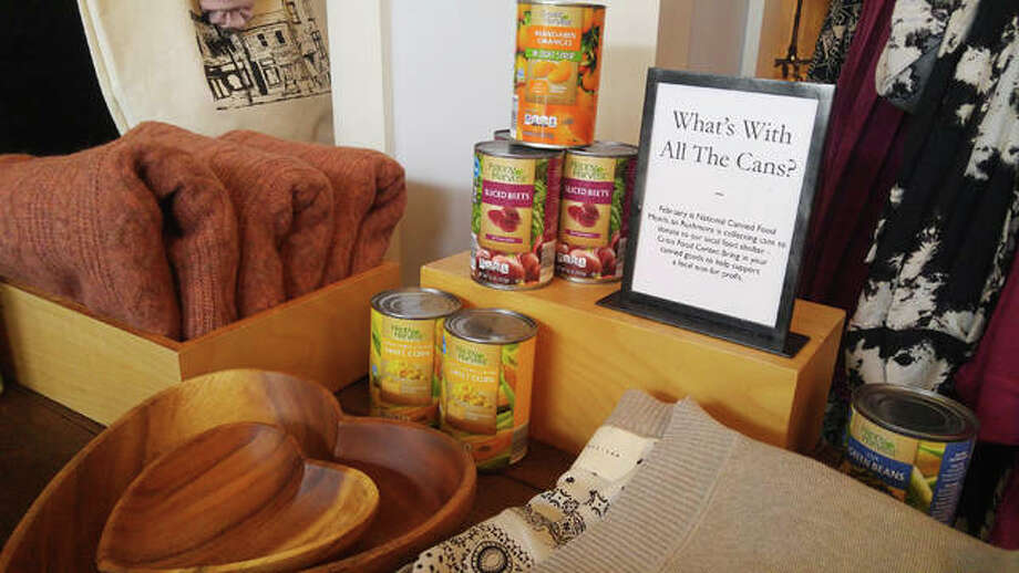 Clothing displays at Rushmore boutique on E. Broadway currently includes canned food items in recognition of National Canned Food Month. Through February, the shop is holding a canned food drive to benefit the Crisis Food Center in Alton. Photo: Jeanie Stephens|The Telegraph