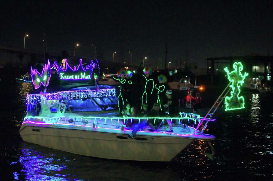 Costumed passengers dance on the deck of a Mardi Gras themed decorated boat as they pass the Kemah Boardwalk. / © 2014 Kirk Sides / Houston Community Newspapers