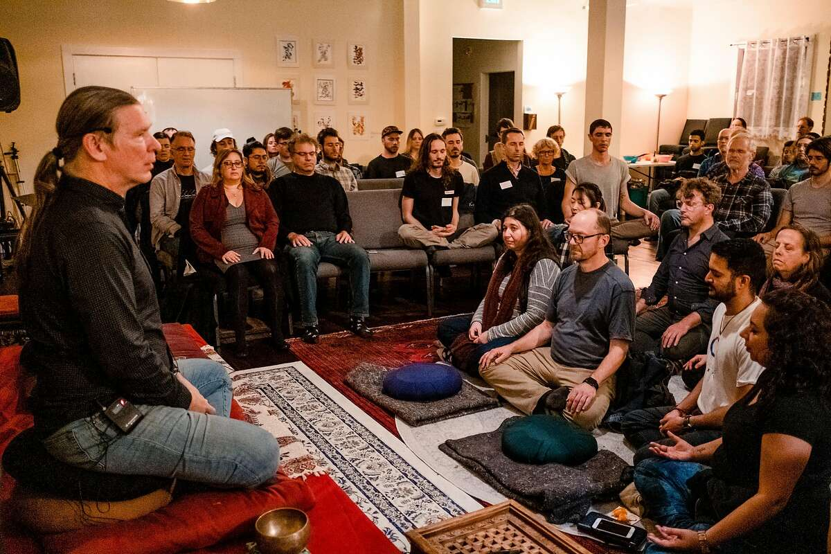 """Michael Taft a teacher at the San Francisco Dharma Collective looks out over a room of attendees as they meditate at the beginning of an event held at the Collective called """"The Promises and Perils of Hacking Consciousness"""" in San Francisco, Calif. on Tuesday January 28, 2020."""