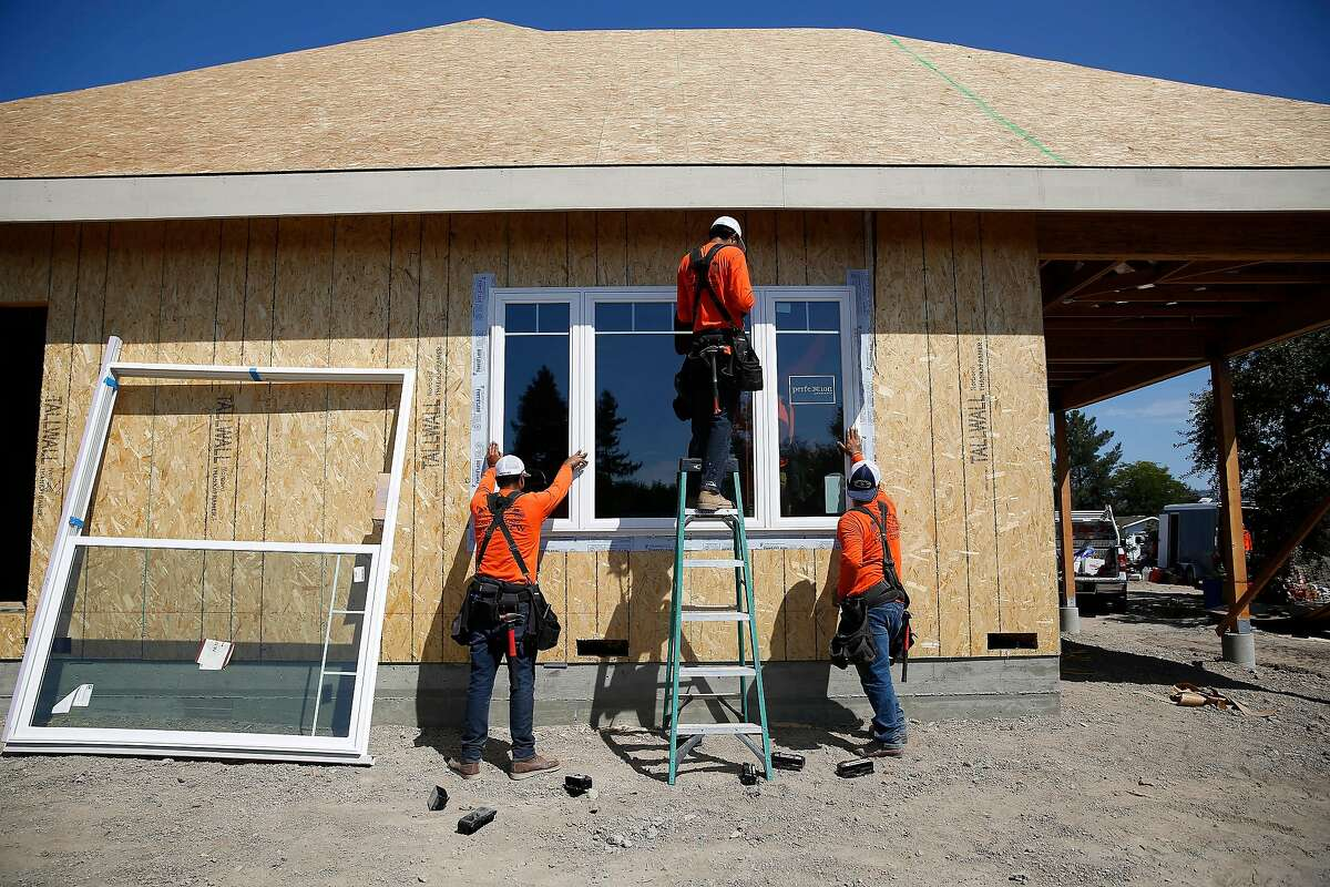 Juan Macias (l to r), Diego Munoz and David Herrera, laborers Wolff Contracting, work to install a window in the the accessory dwelling unit Michael Wolff (not shown), owner Wolf Contracting, is building for his father on Wednesday, September 4, 2019 in Santa Rosa, CA.