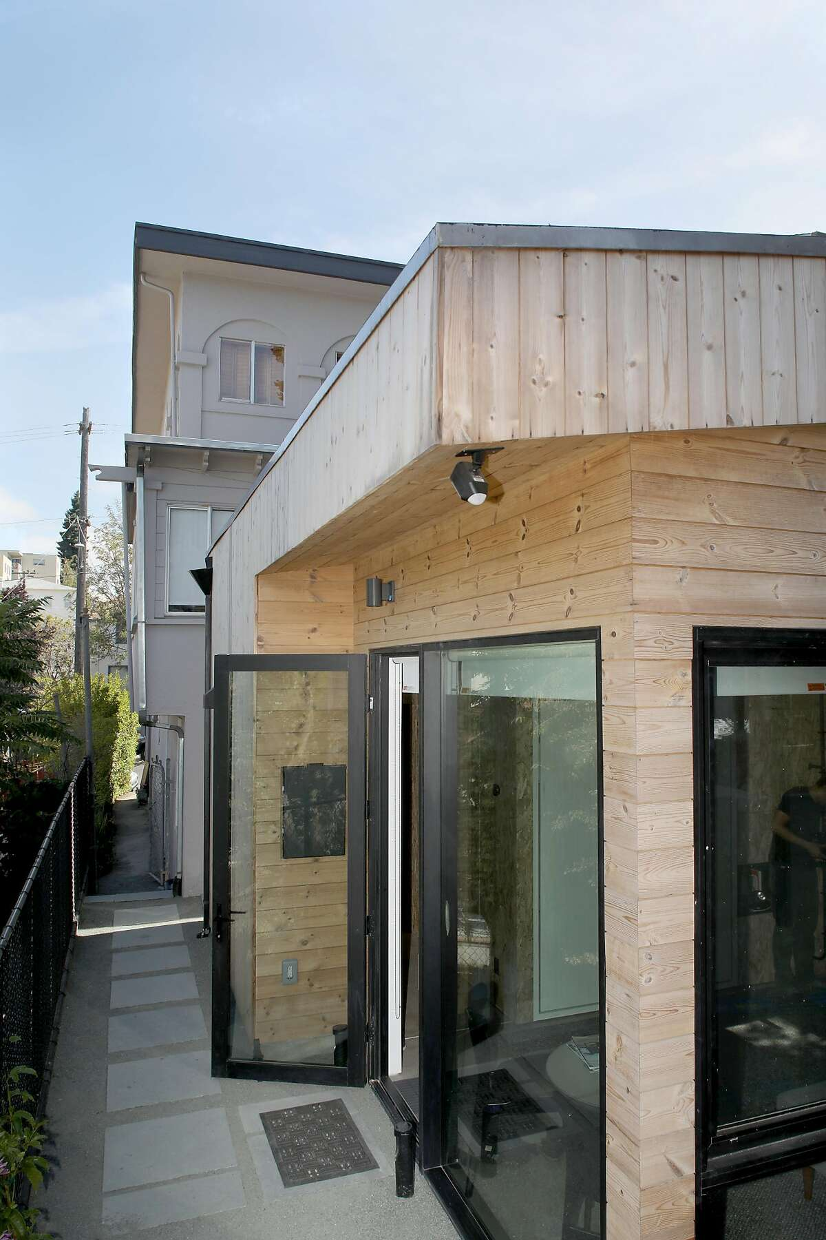 Outside view of �Kleines Haus,� a simple, sleek tiny home designed by architect Peter Liang for his mother, Irmhild tucked behind the house in Oakland Lake Merritt on Thursday, July 18, 2019 in Oakland, Calif.
