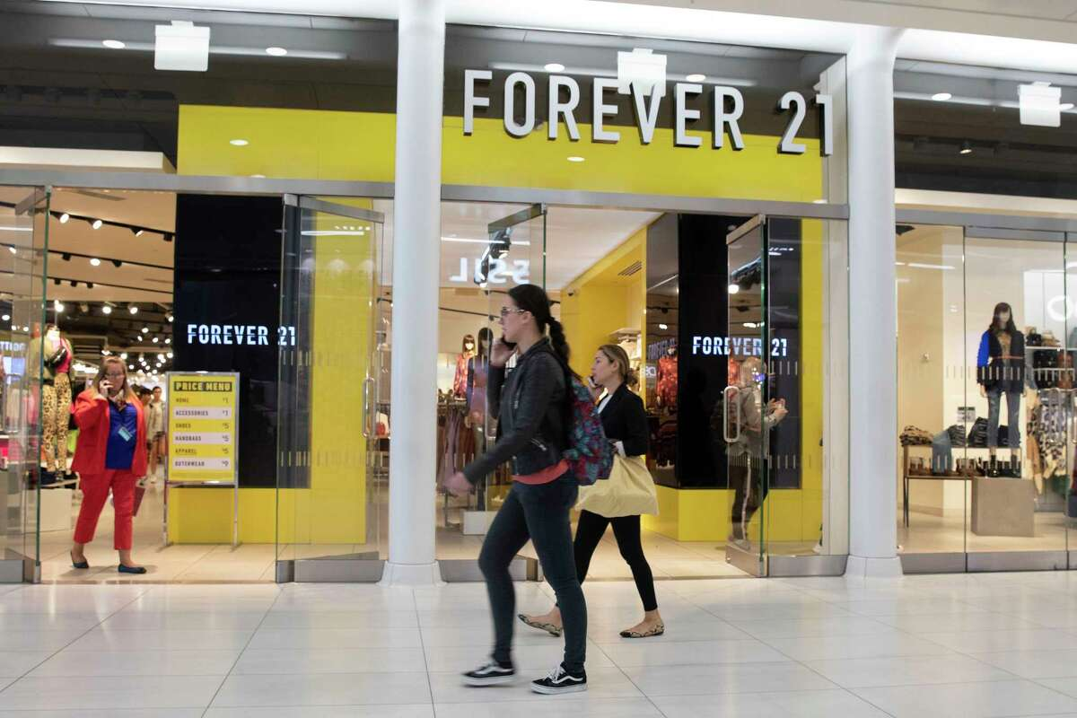 FILE - In a September 30, 2019 file photo, people walk in front of a Forever 21 clothing store in New York. A group that includes mall owners Simon Property Group, Brookfield Property Partners and brand business Authentic Brands Group are offering to buy trendy teen fashion retailer Forever 21 for approximately $81 million.(AP Photo/Mark Lennihan, File)