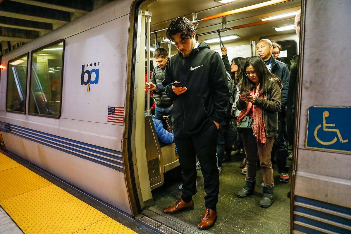 A man (declined name) and others look at their phones as they ride the BART train at the Balboa Park station on Wednesday, Sept. 25, 2019 in San Francisco, California.The Balboa Park station experiences the most cell phone and laptop thefts in the city.
