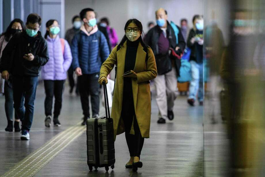 Passengers wear protective face masks as they arrive from Shenzhen to Hong Kong at Lo Wu MTR station, hours before the closing of the Lo Wu border crossing in Hong Kong, on Feb. 3, 2020, amid an outbreak of a coronavirus which began in the Chinese city of Wuhan. Photo: Getty Images / AFP or licensors