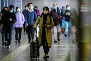 Passengers wear protective face masks as they arrive from Shenzhen to Hong Kong at Lo Wu MTR station, hours before the closing of the Lo Wu border crossing in Hong Kong, on Feb. 3, 2020, amid an outbreak of a coronavirus which began in the Chinese city of Wuhan.
