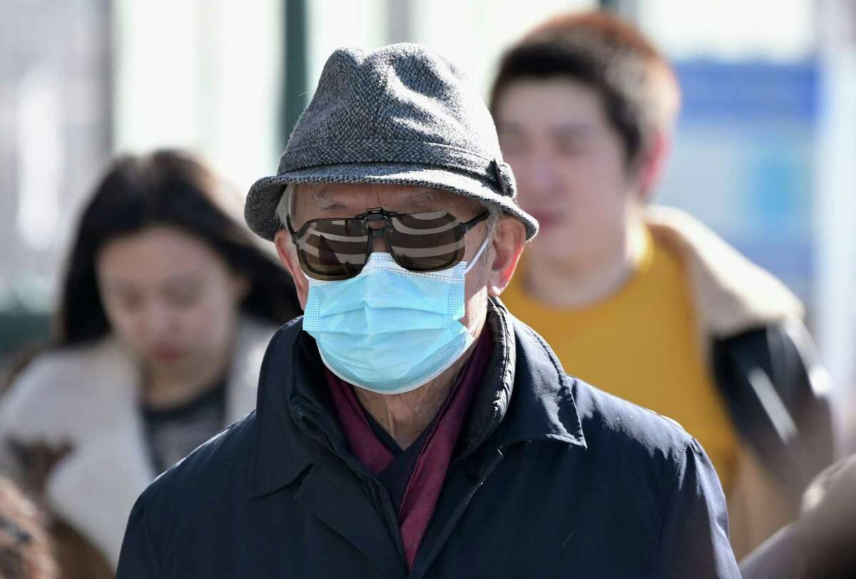 People wear surgical masks in fear of the coronavirus in Flushing, N.Y., on Monday.