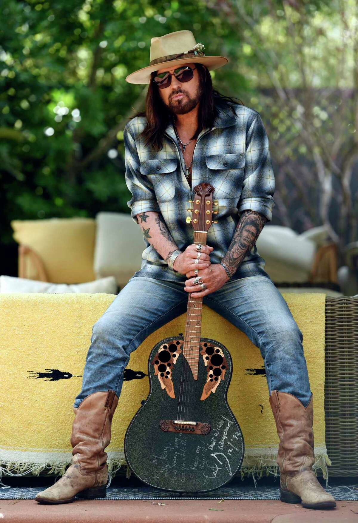 """CORRECTS NAME OF THREE-SONG EP TO """"THE SINGIN' HILLS SESSIONS VOL. 1 SUNSET"""" - Singer-songwriter Billy Ray Cyrus poses for a portrait with an Ovation guitar presented to him by Neil Diamond in 1992, at his home in Los Angeles on Thursday, Jan. 30, 2020. The Kentucky-born singer won his first Grammy this year for his collaboration with rapper Lil Nas X on a€œOld Town Road.a€ Hea€™s releasing a three-song EP on Friday, a€œThe Singin' Hills Sessions Vol. 1 Sunset.a€ (AP Photo/Chris Pizzello)"""