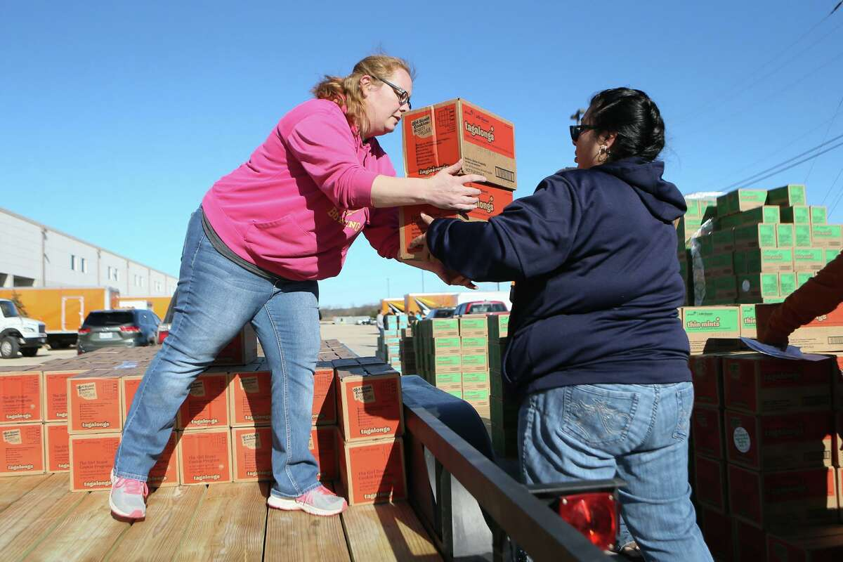 Elizabeth Vorgt, left, with Troop 962, loads some of her troop's 533 cases of cookies onto a trailer with the help of Brenda Acevedo as the Girl Scouts of Southwest Texas begins distribution of close to a million boxes of cookies for 450 troops in its 21-county district.