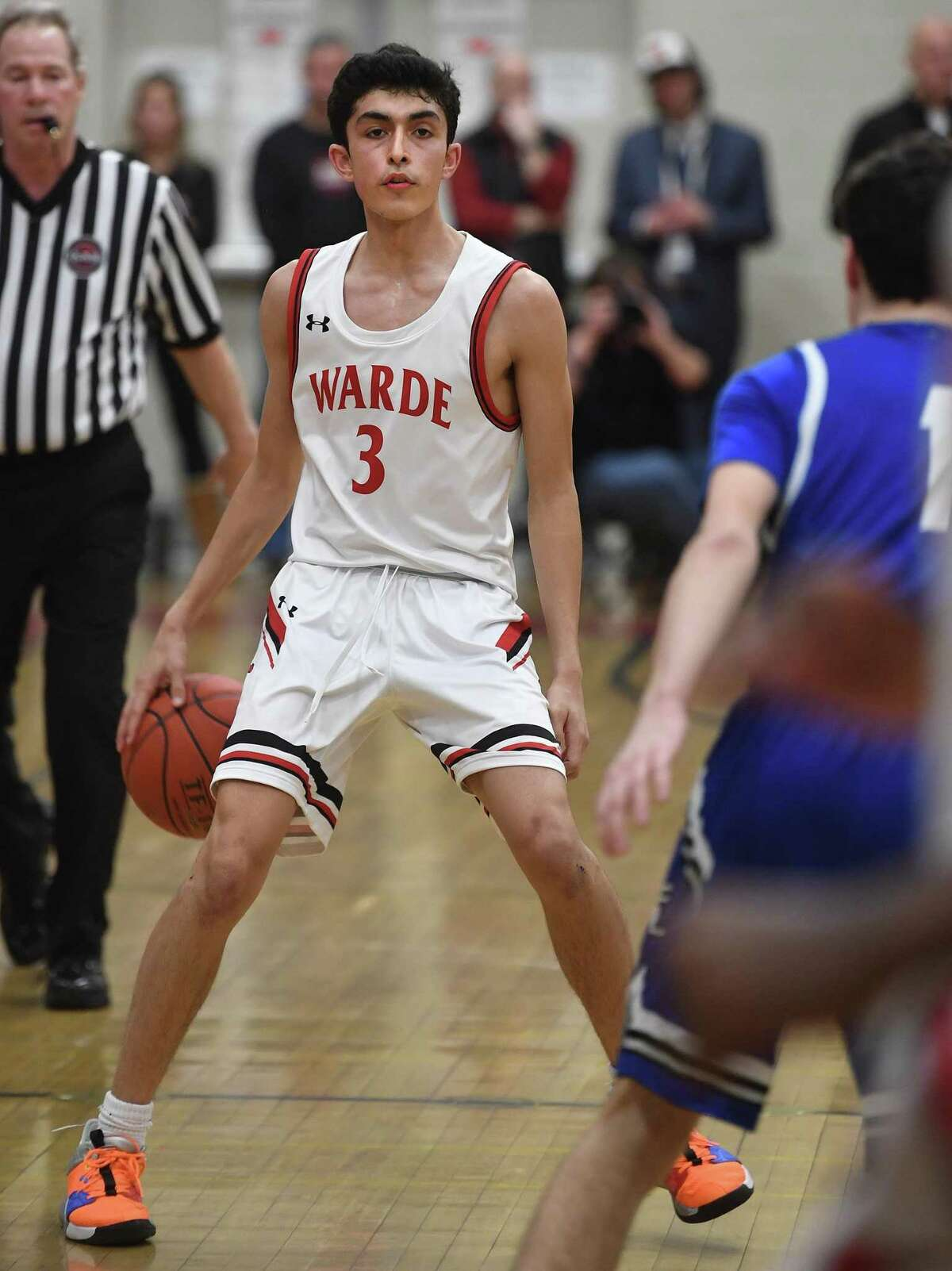 Warde point guard Brendan McMahon dribbles behind his back as he surveys the defense in the first half of their boys basketball game with rival Ludlowe at Warde High School in Fairfield, Conn. on Monday, February 03, 2020.