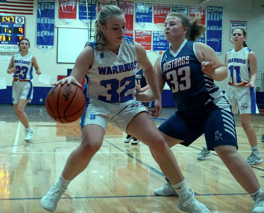 Chippewa Hills sophomore Taylor Neeb protects the ball from Montabella senior Morgan Christensen near the baseline during CH's win on Monday night at home. (Pioneer photo/Judd)