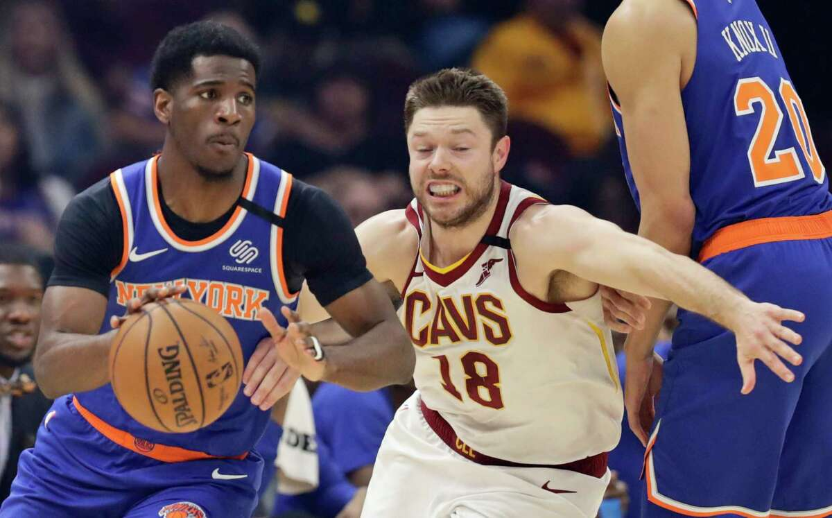 New York Knicks' Damyean Dotson, left, drives past Cleveland Cavaliers' Matthew Dellavedova in the first half of an NBA basketball game, Monday, Feb. 3, 2020, in Cleveland. (AP Photo/Tony Dejak)