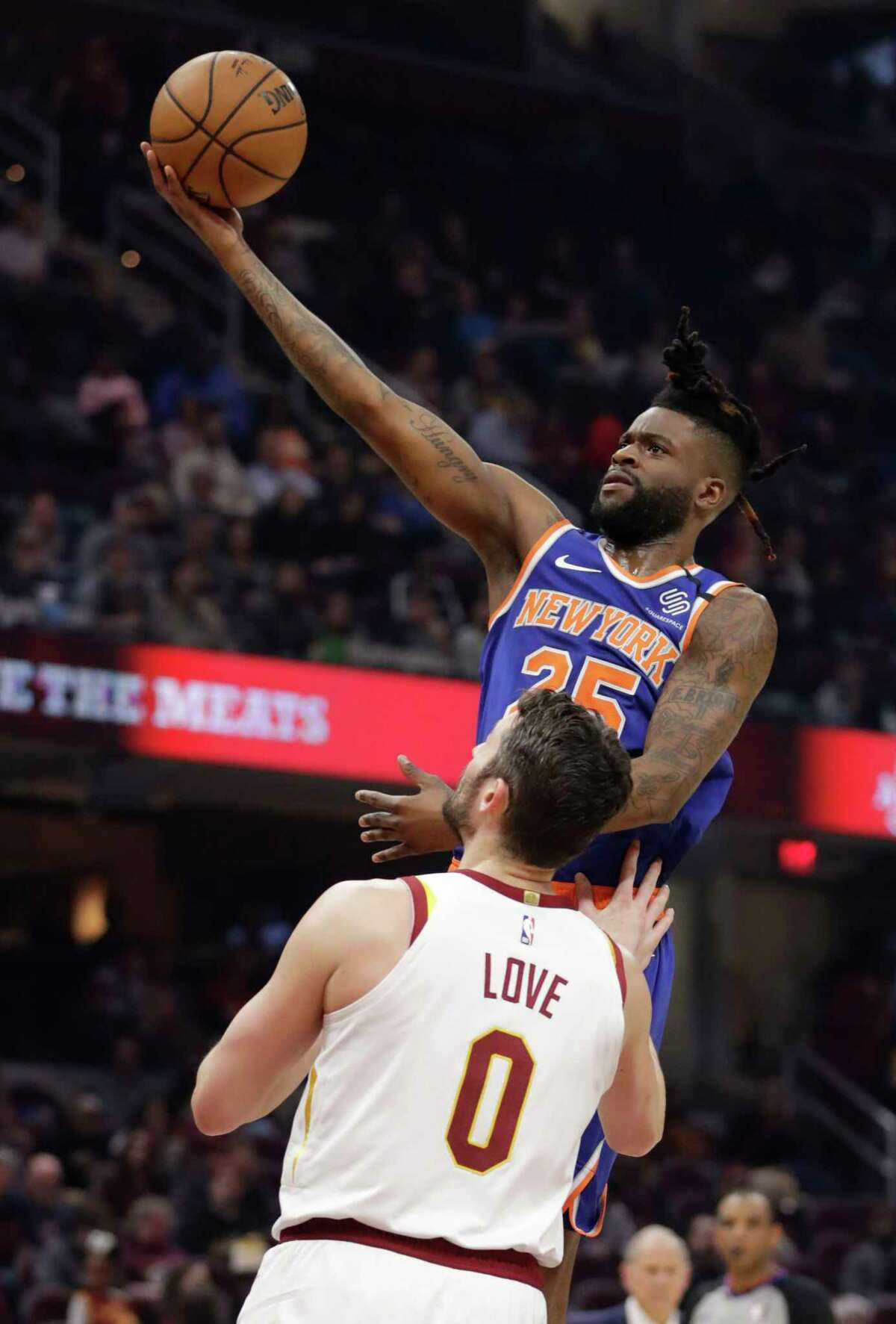New York Knicks' Reggie Bullock (25) drives to the basket against Cleveland Cavaliers' Kevin Love (0) in the second half of an NBA basketball game, Monday, Feb. 3, 2020, in Cleveland. New York won 139-134 in overtime. (AP Photo/Tony Dejak)