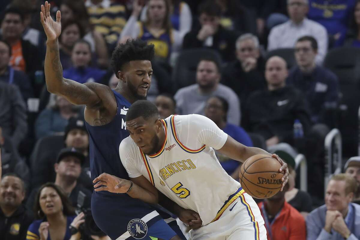 Golden State Warriors forward Kevon Looney (5) drives against Minnesota Timberwolves forward Jordan Bell during the first half of an NBA basketball game in San Francisco, Monday, Dec. 23, 2019. (AP Photo/Jeff Chiu)