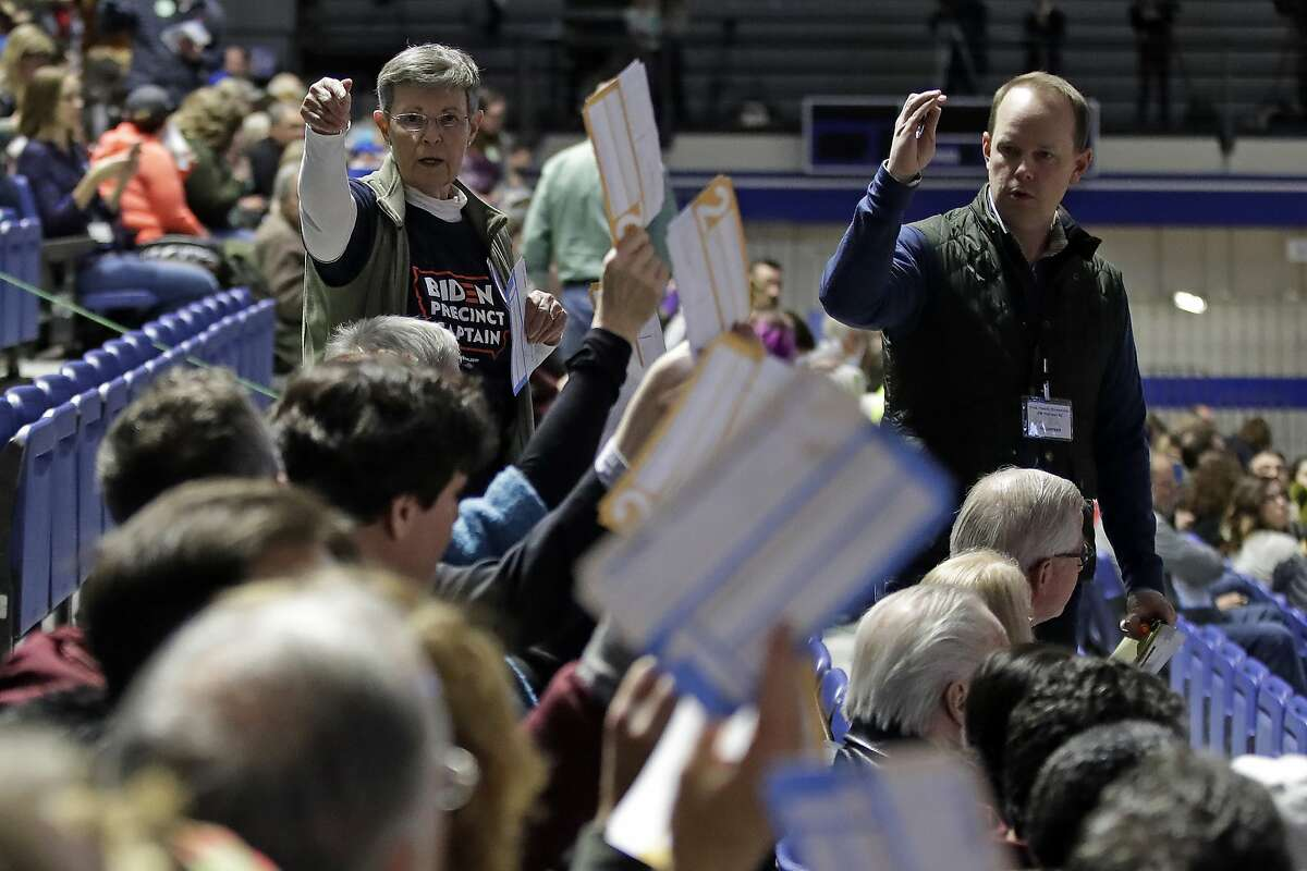 Caucus goers seated in the section for Democratic presidential candidate former Vice President Joe Biden hold up their first votes as they are counted at the Knapp Center on the Drake University campus in Des Moines, Iowa, Monday, Feb. 3, 2020.