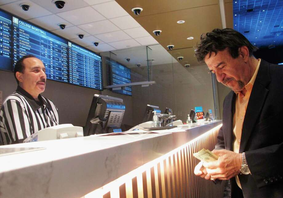 In this Jan. 29, 2020 photo, a man makes a bet on the upcoming Super Bowl at Bally's casino in Atlantic City, N.J. Business was brisk at sports books around the country on Super Bowl Sunday, with customers risking money on everything from the coin toss at the start of the game, to the color of the Gatorade dumped on the winning coach, Kansas City's Andy Reid, at the end of it. (AP Photo/Wayne Parry) Photo: Wayne Parry / Associated Press / Copyright 2020 The Associated Press. All rights reserved.