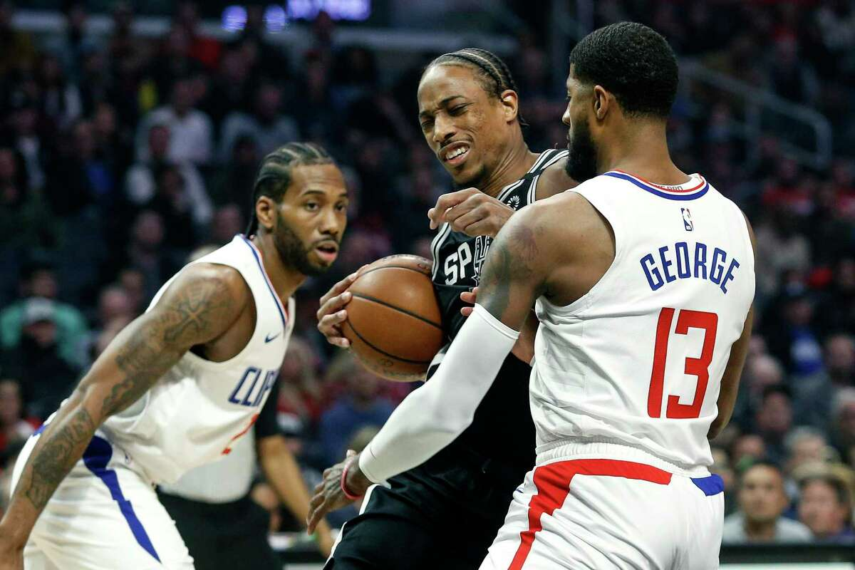 San Antonio Spurs' DeMar DeRozan, center, drives against Los Angeles Clippers' Paul George (13) during the first half of an NBA basketball game, Monday, Feb. 3, 2020, in Los Angeles. (AP Photo/Ringo H.W. Chiu)