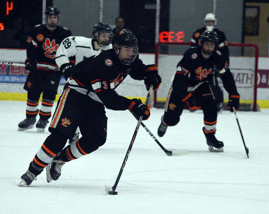 Edwardsville's Mark Tucker, left, controls the puck during the third period of Monday's game against Marquette at the Maryville Hockey Center. Photo: Scott Marion/The Intelligencer
