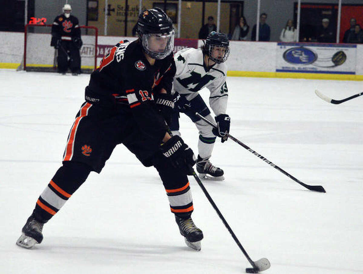 Edwardsville's Aidan Stevens skates past a Marquette defender during the third period of Monday's game at the Maryville Hockey Center.