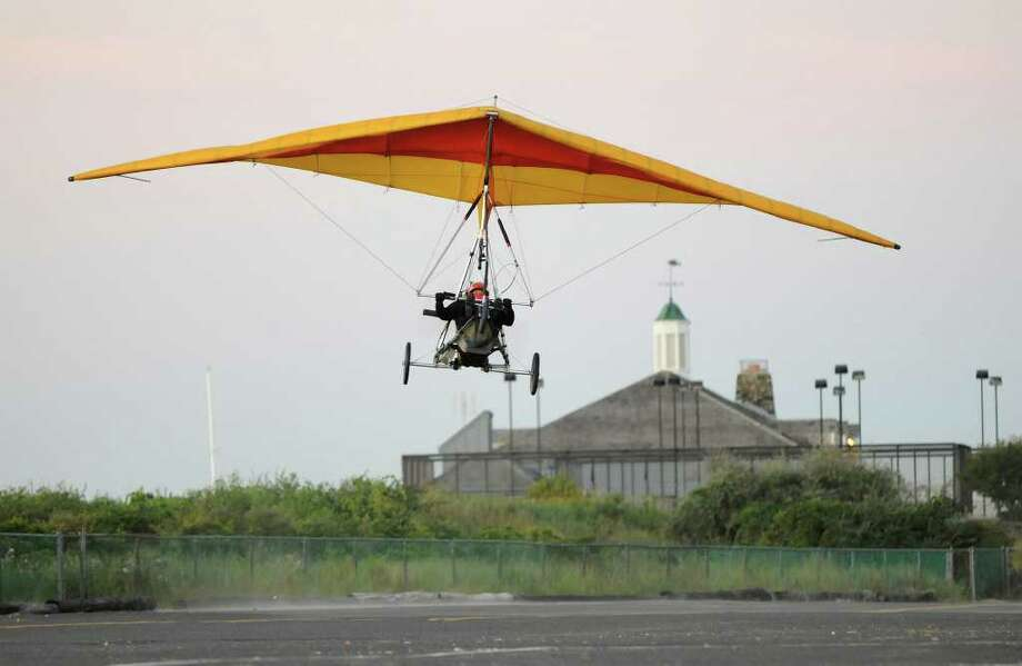 "Andy Kosch, Fairfield, takes off in an ultralight aircraft at Jennings Beach in Fairfield at daybreak on August 14, 2010. Kosch is commemorating the flight of Gustave Whitehead, who, according to many people, flew very near this same spot on the same date in 1901, two years before the Wright Brothers' first flight. Kosch, a teacher at Platt Technical High School, used to teach hang gliding at Sturges Park, just behind what is now Fairfield Ludlowe High School, and became interested in Whitehead's accomplishments years ago when he realized Whitehead's aircraft had a similar wing design to a hang glider. While he has flown a replica of Whitehead's aircraft, today's flight was more a commemoration, as the ultralight is easier to maneuver.  ""I want the schoolkids in this area to know the history of flight here,"" he said, ""sometimes things happen in history that don't get credit."" Kosch circled above Captain's Cove in nearby Bridgeport, then returned and landed back at Jennings Beach. Photo: Shelley Cryan / Shelley Cryan for the CT Post"