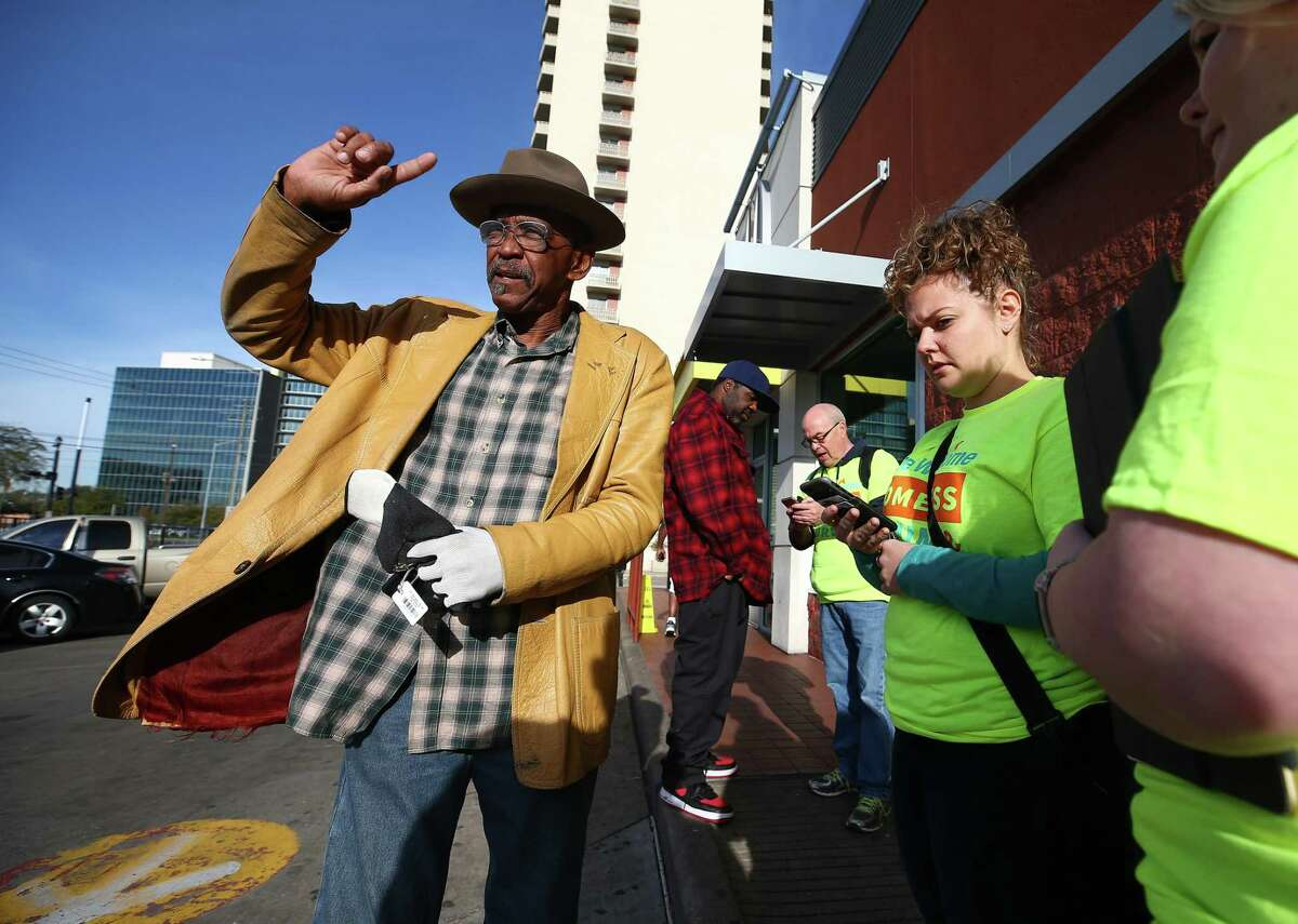 Charles Mitchell, left answers survey questions from Meg Pohodich, right, during the annual count of the Houston homeless population in 2018.
